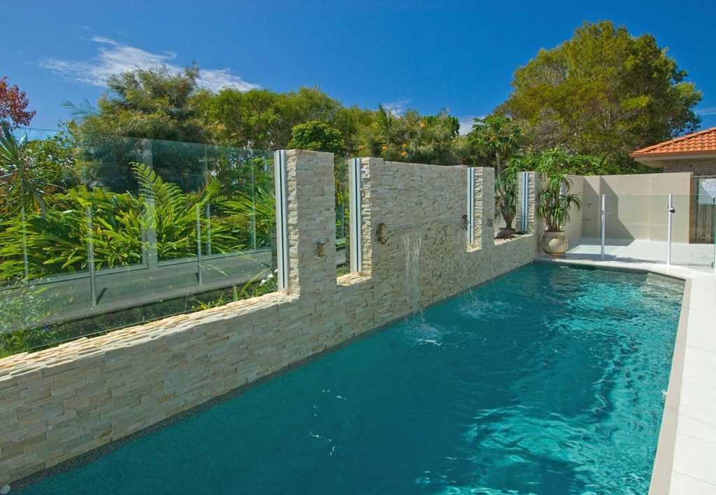Swimming pool with stack stone wall feature