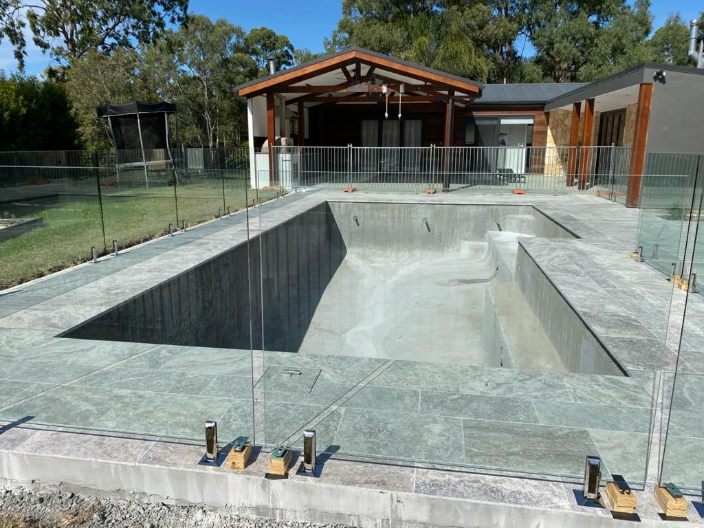 concrete swimming pool under construction with tiles, fencing, and shell all complete