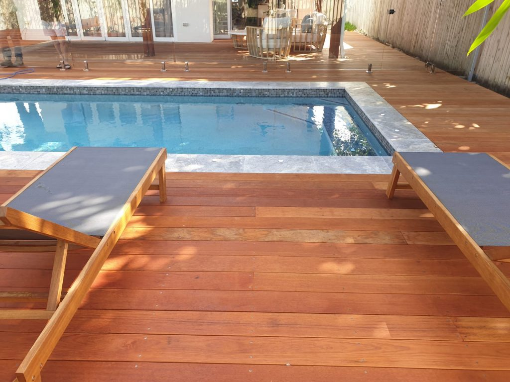 Relax in these sun-baking lounges that tie in with the timber decking around this modern swimming pool.